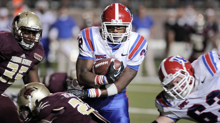 Louisiana Tech's Kenneth Dixon, center, evades Texas State's Tylond Robertson, left, and Phillip Benning behind teammate Stephen Warner, right, during the second half of an NCAA college football game on Saturday, Nov. 10, 2012, at Texas State University in San Marcos, Texas. (AP Photo/Darren Abate)