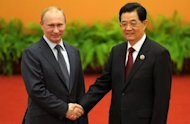 Russia's President Vladimir Putin and Chinese President Hu Jintao, pictured at a summit of the Shanghai Cooperation Organization (SCO) in Beijing. A regional group led by Russia and China said it opposed military intervention in the Middle East, a day after the Syrian opposition accused forces loyal to the regime of massacring 100 people