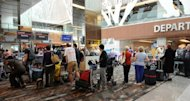 This file photo shows passengers queuing at a check-in counter in Singapore&#39;s Changi International Airport, in 2011. Singapore police warned on Tuesday that members of a Chinese crime syndicate were believed to be stealing money from the bags of passengers while they slept on flights to and from the country