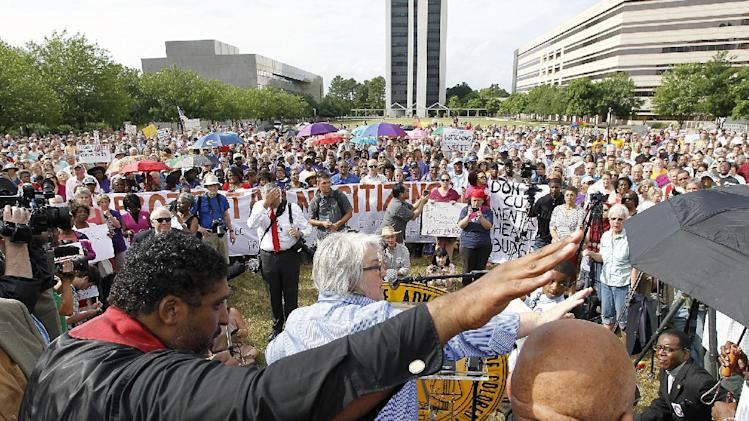 The Rev. William Barber, left, of the NC NAACP and Pastor Mary Petty of Pullen Memorial Baptist Church, center, wave at a rally on Halifax Mall as the Monday protests are held at the General Assembly in Raleigh, NC on Monday, June 3, 2013. More than 100 people have been arrested in the largest demonstrations yet in the state chapter of the NAACP's campaign against the Republican-led General Assembly. Police estimate that roughly 1,000 people attended a rally late Monday afternoon behind the Legislative Building on Halifax Mall. Hundreds later entered the building, with those intending to get arrested wearing green wrist bands. (AP Photo/The News & Observer, Chris Seward) MANDATORY CREDIT