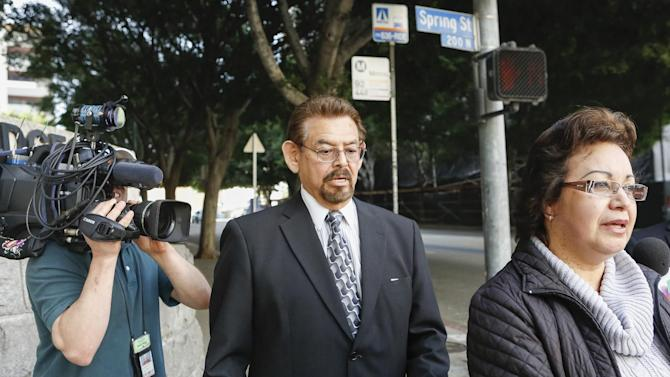 George Mirabal, a former Bell City elected official, middle, walks with unidentified members of his family,after a guilty verdict was read in his trial on Wednesday, March 20, 2013, in Los Angeles. Mirabal and four former elected officials were convicted of multiple counts of misappropriation of public funds, and a sixth defendant was cleared entirely. Former Mayor Oscar Hernandez and co-defendants Mirabal, George Cole, Teresa Jacobo, and Victor Belo were all convicted of multiple counts and acquitted of others. The charges against them involved paying themselves inflated salaries of up to $100,000 a year in the city of 36,000 people, where one in four residents live below the poverty line. (AP Photo/Damian Dovarganes)