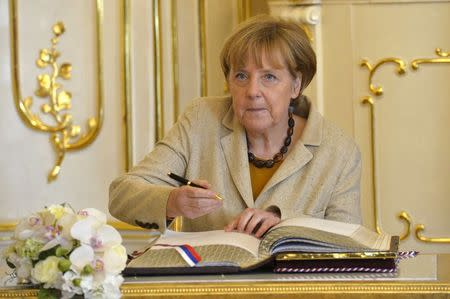 German Chancellor Merkel signs a guest book at the presidential palace in Bratislava