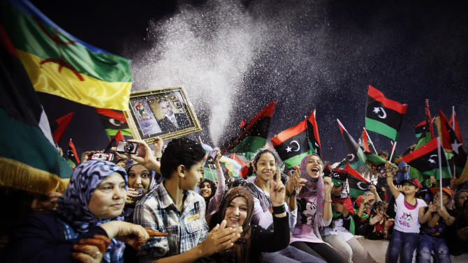 FILE - In this Sunday, Oct. 23, 2011 file photo, people celebrate the end of the civil war after the capture and death of Moammar Gadhafi at Martyrs' Square in Tripoli, Libya. (AP Photo/Abdel Magid al-Fergany, File)