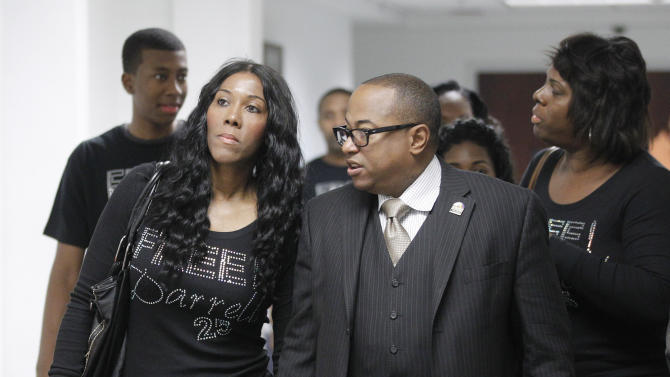 Alice Williams, left, arrives at her son Darrel Williams' sentencing hearing with Bishop Travis Grant, right, National Field director for Rainbow/PUSH Coalition, in Stillwater, Okla. on Friday, Oct. 12, 2012. Ex-Oklahoma State basketball player Darrell Williams avoided more time behind bars Friday when a judge gave him a suspended sentence in a sexual assault case in which Williams insisted he was innocent. (AP Photo/Sue Ogrocki)