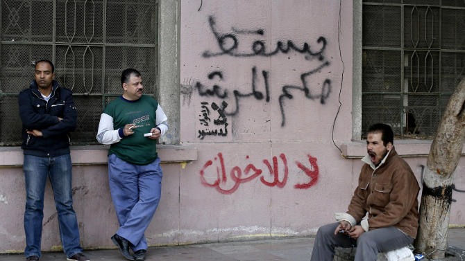 "Egyptian men stand near Arabic writing on a wall in Arabic that reads, ""down with the leader's rule, no to the Muslim Brotherhood,"" in Tahrir Square in Cairo, Egypt, Sunday, Dec. 9, 2012. Egypt's liberal opposition has called for more protests on Sunday after the president made concessions overnight that fell short of their demands to rescind a draft constitution going to a referendum on Dec. 15. (AP Photo/Hassan Ammar)"