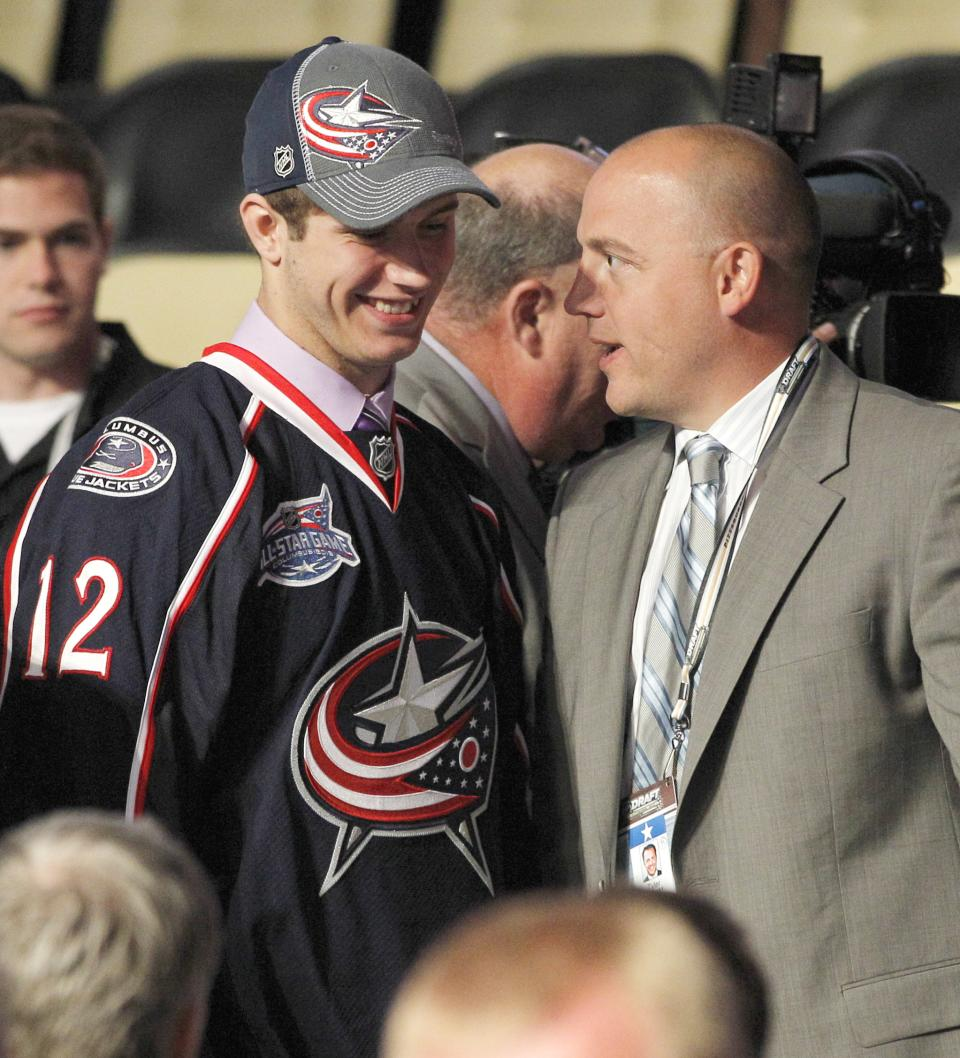 Ryan Murray, left, a defenseman, stands with officials from the Columbus Blue Jackets at their table after being chosen second overall in the first round of the NHL hockey draft on Friday, June 22, 2012, in Pittsburgh. (AP Photo/Keith Srakocic)