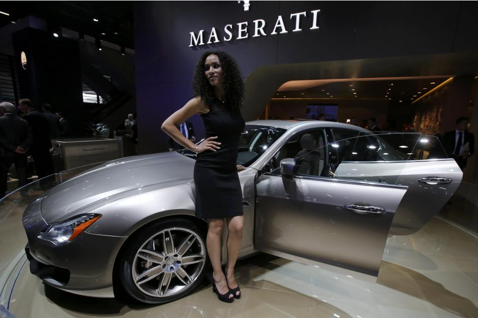 A model poses next to a Maserati quattroporte during a media preview day at the Frankfurt Motor Show