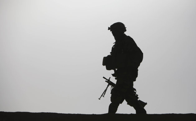 FILE - In this Monday, Feb. 15, 2010 file photo, a British soldier walks with his machine gun on the roof of a residential house in the village Qari Sahib, Nad Ali district, Helmend province, southern Afghanistan. Young men who have served in the British military are about three times more likely than civilians to have committed a violent offense, researchers reported Friday, March 15, 2013 in a study that explores the roots of such behavior. The research found that merely being sent to Iraq or Afghanistan made no difference in rates of violent crime later on. Instead, a key predictor was violent behavior before enlisting. (AP Photo/Altaf Qadri, File)