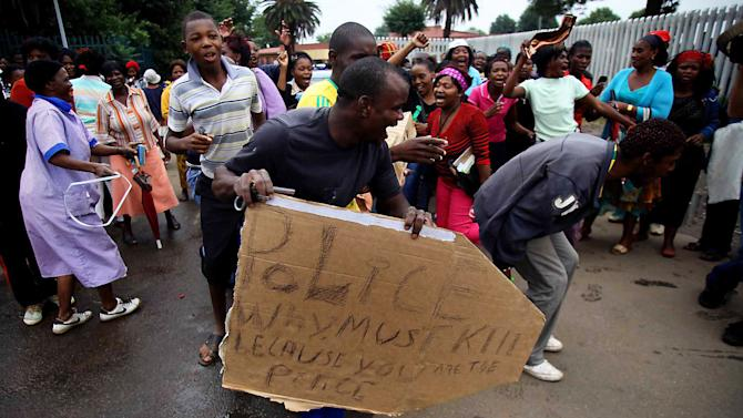 Residents protest the death of Mozambican taxi driver Mido Macia outside a local police station, in Daveyton, near Johannesburg, South Africa, Friday, March 1, 2013. Eight South African police officers were charged with murder on Friday for the death of a taxi driver dragged by a police vehicle, a videotaped incident which became a worldwide symbol of police brutality in this country. (AP Photo)