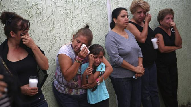 Family members of Vigilante leader Hipolito Mora cry before he and other vigilantes leave to voluntarily cooperate in a shootout investigation in La Ruana, Michoacan