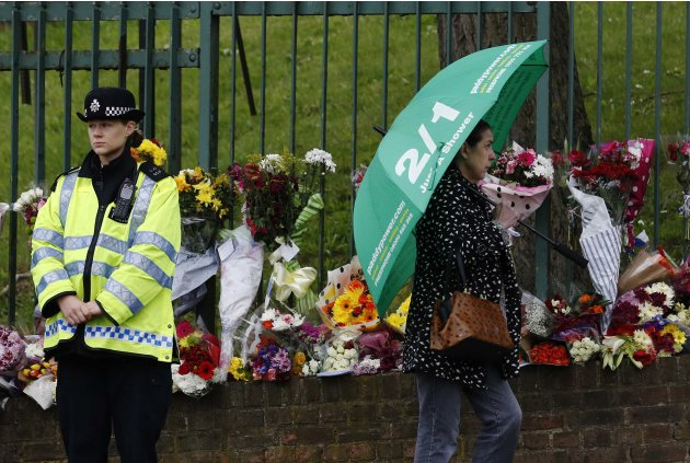 A police woman stands by floral tributes for Drummer Lee Rigby of the British Army near the scene of his killing in Woolwich