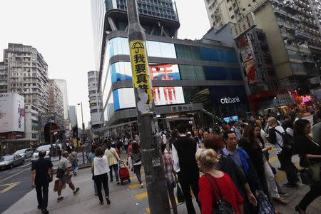 """Part of a sticker that reads """"I want true universal suffrage"""" is seen on a lamp post at the intersection of Nathan Road and Argyle Street at Mongkok shopping district in Hong Kong"""