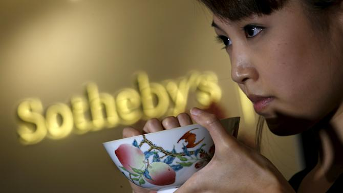 "A staffer at Sotheby's shows a rare Famille-Rose ""Peach"" bowl mark and period of Yongzheng, during a preview in Hong Kong"