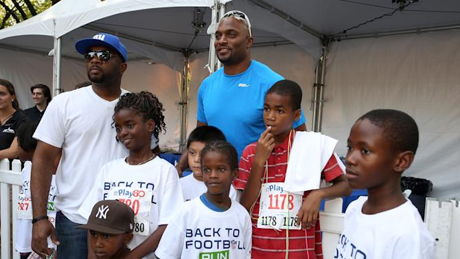 Former NFL wide receiver Amani Toomer, center back row, is seen during the National Football League Back to Football Run on Friday, Aug. 30, 2012 at Central Park in New York. (John Minchillo/AP Images for NFL)