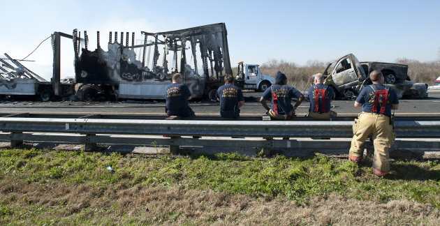 Firemen watch as cleanup crews work on vehicles that were involved in a multi-vehicle accident that killed at least nine people, on Interstate 75 near Gainesville, Fla., Sunday, Jan. 29, 2012. Authori