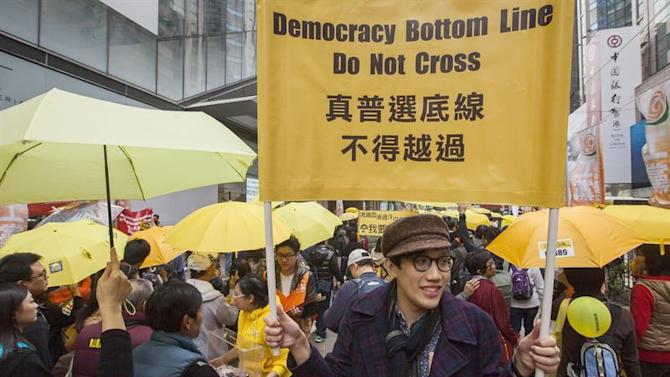 . Hong Kong (China), 01/02/2015.- A protester from Hong Kong's Umbrella Movement holds a banner calling for democratic reform as they march through the streets calling for genuine universal suffrage, Hong Kong, China, 01 February 2015. Pro-democracy activists took to the streets for their first rally since authorities put an end to their nearly three months of protests last year. Thousands gathered at Victoria Park in Hong Kong's Causeway Bay area to call for full democratic elections of the Chinese territory's chief executive. They object to a plan drawn up by Beijing that sees candidates for the city's chief executive pre-selected by a pro-Beijing committee before elections in 2017. (Elecciones, Protestas) EFE/EPA/ALEX HOFFORD (Elecciones, Protestas) EFE/EPA/ALEX HOFFORD