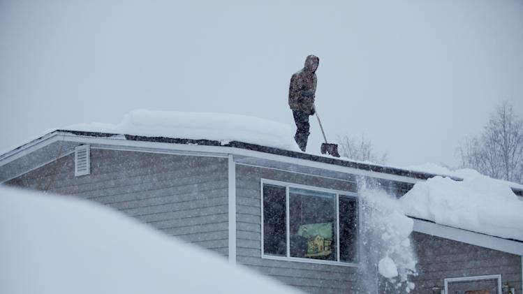 14-year-old Doug Hamrick shovels snow off of his family's roof Thursday, Jan.12, 2012, in Anchorage. The National Weather Service is predicting a total snowfall of 8 to 16 inches today, putting Anchorage on track to have the snowiest winter on record. (AP Photo/Loren Holmes)
