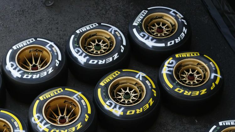 A Lotus Formula One technician sits on tyres ahead of the weekend's Belgian Grand Prix in Spa-Francorchamps