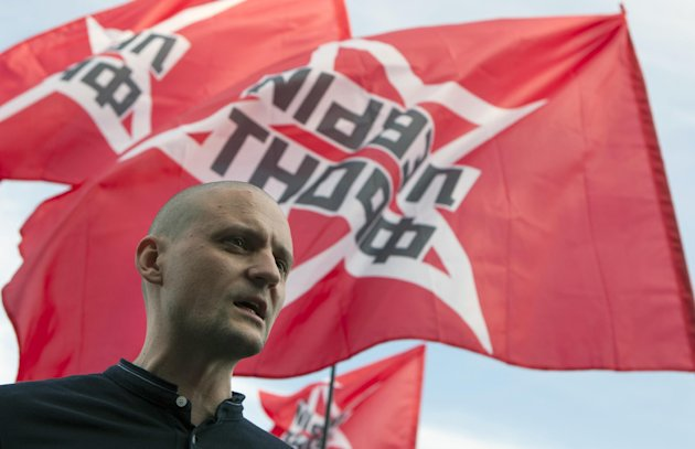 Left Front leader Sergei Udaltsov, with his movement flags in the background, speaks at an opposition rally in support of opposition activists they allege were arrested over their role in a violent protest in May, in Moscow, Thursday, July 26, 2012. Opposition activists and rights groups called the arrests a part of a widening government crackdown on dissent that followed Vladimir Putin&#39;s election to a third presidential term in March. (AP Photo/Alexander Zemlianichenko)