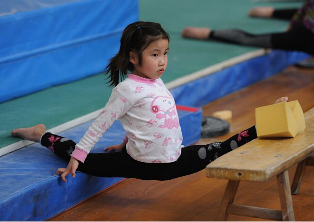 In a photograph taken on April 7, 2012, a young Chinese gymnast trains at a special sport school in Hefei, east China's Anhui province. Potential gymnasts embark on a gruelling schedule which aims