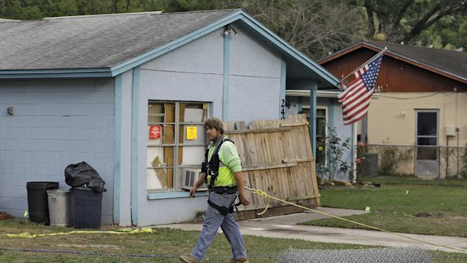 An engineer, tethered with a safety line, walks in front of a home where a sinkhole opened up underneath a bedroom late Thursday evening and swallowed a man in Seffner, Fla. on Saturday, March 2, 2013.   Jeffrey Bush, 37, was in his bedroom Thursday night when the earth opened and took him and everything else in his room. Five other people were in the house but managed to escape unharmed. Bush's brother jumped into the hole to try to help, but he had to be rescued himself by a sheriff's deputy.  (AP Photo/Chris O'Meara)