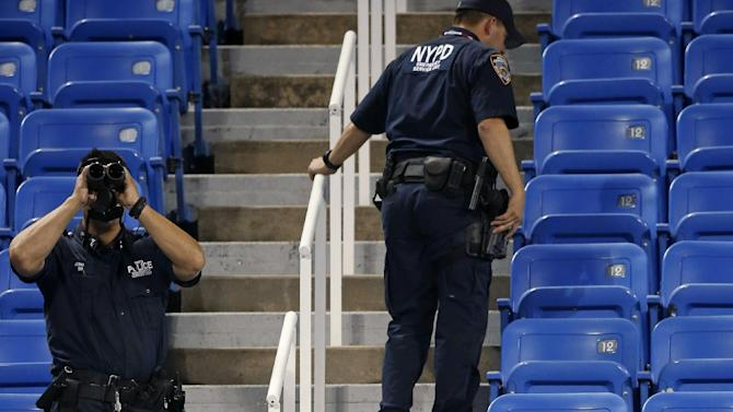 Police officers investigate the southwest corner of Louis Armstrong Stadium after a drone flew over the court, buzzing the players during a match between Flavia Pennetta, of Italy, and Monica Niculescu, of Romania, during the second round of the U.S. Open tennis tournament in New York, Thursday, Sept. 3, 2015. The drone crash-landed in the seats and can be seen to the right of the police officer on his phone. (AP Photo/Kathy Willens)