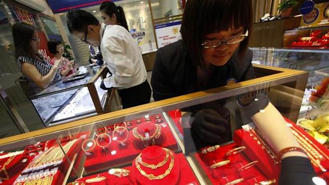 An employee arranges gold jewellery as customers shop at a MoneyMax pawn shop outlet in Singapore August 23, 2013. REUTERS/Edgar Su/Files
