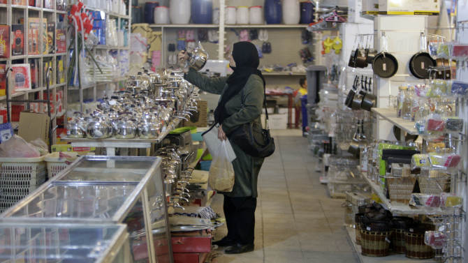 In this photo taken on Wednesday, Oct. 24, 2012, an Iranian woman inspects a kettle in a home appliance store in Tehran, Iran. Iranian authorities have been forced to quell protests in recent weeks over the plummeting value of the country's currency which lost nearly 40 percent of its value against the U.S. dollar in a week in early October. With the U.S. election less than 10 days away, both President Obama and Republican challenger Mitt Romney are cautious about discussing potential compromises as Iran's economy shows signs of increasing strain from economic sanctions that seek nuclear concessions. (AP Photo/Vahid Salemi)
