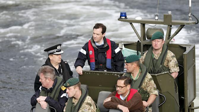 Britain's Chancellor of the Exchequer Osborne arrives by boat at the jetty at the Royal Navy's submarine base at Faslane