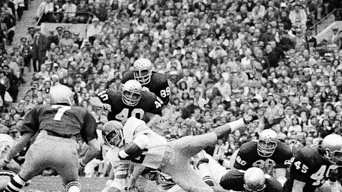 FILE - In this Oct. 27, 1973, file photo, Notre Dame's Greg Collins, bottom right, tries to make the tackle as Southern California's Anthony Davis reaches for a 4-yard gain during the first quarter of their NCAA college football game in South Bend, Ind. Notre Dame's Tim Rudnick (7), Gary Potempa (40), Ross Browner (89) and Mike Fanning (88) help on the play. Three field goals by Bob Thomas, an 85-yard touchdown run by Eric Penick and stingy run defense helped Notre Dame end Southern California's winning streak at 23 games with a 23-14 victory. The Associated Press takes a look at some of the memorable games in college football's greatest intersectional rivalry in anticipation of Southern California hosting No. 1 Notre Dame on Saturday, Nov. 24, 2012. (AP Photo/Charles Knoblock, File)