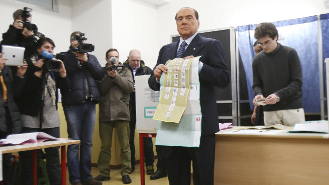 Former Premier Silvio Berlusconi shows his ballots prior to voting in Milan, Italy, Sunday, Feb. 24, 2013. Italy votes in a watershed parliamentary election Sunday and Monday that could shape the future of one of Europe's biggest economies. (AP Photo/Antonio Calanni)