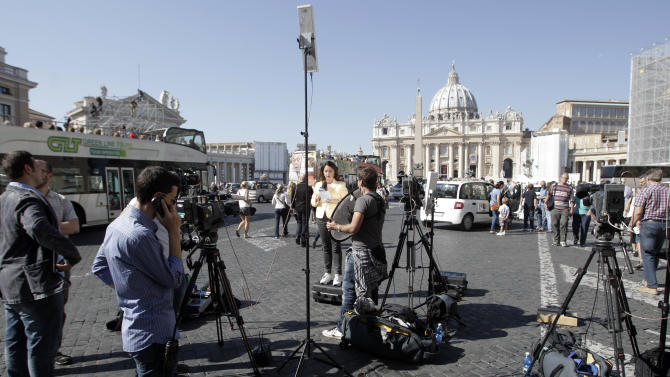 TV journalists stand up in front of the Vatican, Saturday, Oct. 6, 2012. The verdict in the case of the pope's butler accused of leaking papal documents  is expected Saturday Oct. 6, 2012, and may help close one of the most damaging scandals of Pope Benedict XVI's papacy. (AP Photo/Riccardo De Luca)