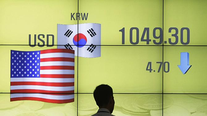 A man walks past a screen showing the exchange rate between the U.S. dollar and the South Korean won in Seoul, South Korea, Monday, Aug. 1, 2011. South Korean stocks rose 39.1 points, or 1.83 percent , to close at 2,172.31, Monday as foreign investors scooped up blue-chip auto and tech exporters on hopes that the U.S. Congress would approve the U.S. debt limit increase. (AP Photo/Ahn Young-joon)