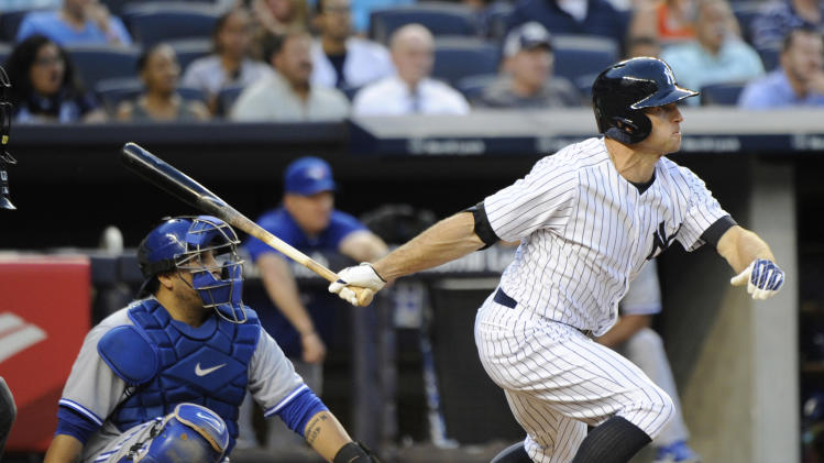 New York Yankees' Brett Gardner hits a sacrifice fly to score a run as Toronto Blue Jays catcher Dioner Navarro, left, looks on during the second inning of a baseball game Friday, July 25, 2014, at Yankee Stadium in New York. (AP Photo/Bill Kostroun)