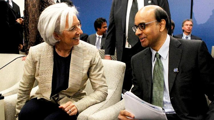International Monetary Fund (IMF) Managing Director Christine Lagarde, left, talks with IMFC Chair Tharman Shanmugaratnam during the World Bank IMF Spring Meetings in Washington, Saturday, April 20, 2013. (AP Photo/Molly Riley)