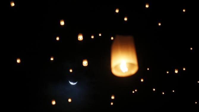 The moon is seen behind lanterns released by survivors, local residents and visitors during the ceremony for victims of 2004 tsunami in Ban Nam Khemve