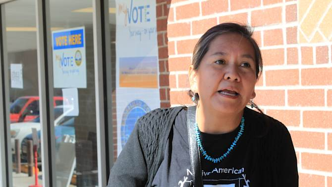 In this Oct. 26, 2012, photo, Laurie Weahkee, executive director of the Native American Voters Alliance, talks to a group of Native American voters outside an early voting center in Albuquerque, N.M. NAVA, the National Congress of American Indians and other groups have been working to turn around low voter participation that has persisted in Indian Country for decades. (AP Photo/Susan Montoya Bryan)