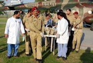 Army doctors move Malala Yousafzai, 14, from a helicopter to an army hospital. A Pakistani schoolgirl shot in the head by the Taliban showed signs of improvement by moving her limbs Saturday, the military said, though she remains unconscious and on a ventilator