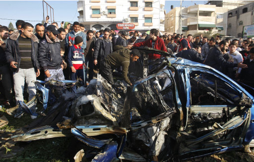 Palestinians gather around the wreckage of a car targeted in an airstrike in Gaza City, Friday, March 9, 2012. An Israeli airstrike killed top Palestinian militant commander Zuhair al-Qaissi and a second militant in Gaza on Friday in the highest profile attack against the coastal strip in months. (AP photo/Hatem Moussa)