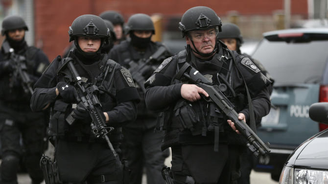 FILE - In this Friday, April 19, 2013 file photo, police in tactical gear conduct a search for a suspect in the Boston Marathon bombings, in Watertown, Mass. The bombs that blew up seconds apart near the finish line of the Boston Marathon left the streets spattered with blood and glass, and gaping questions of who chose to attack and why. Since Monday, Boston has experienced five days of fear, beginning with the marathon bombing attack, an intense manhunt and much uncertainty ending in the death of one suspect and the capture of the other. (AP Photo/Matt Rourke, File)