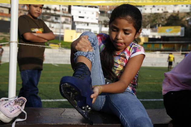 A girl puts on her ice skates before skating in an artificial ice rink set by the Town Hall at the slum district of Petare in Caracas
