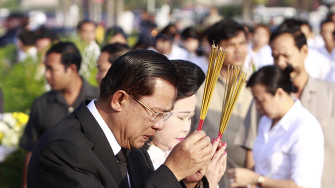Cambodia's Prime Minister Hun Sen and his wife Bun Rany pray with incenses sticks during a Buddhist ceremony for the victims near the site where people stampeded during Monday's water festival in Phnom Penh, Thursday, Nov. 25, 2010. (AP Photo/Heng Sinith)