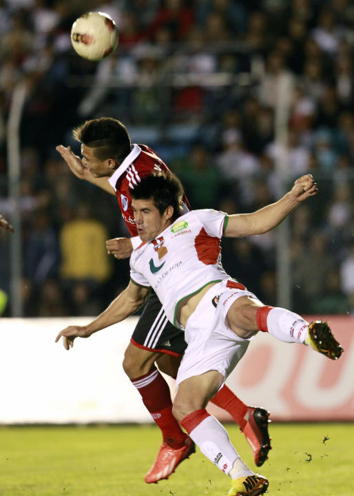 River Plate's Teofilo Gutierrez of Argentina, back, heads the ball against Liga Deportiva Universitaria de Loja's Oscar Ayala of Ecuador during a Copa Sudamericana soccer match  in Loja, Ecuador, Thur
