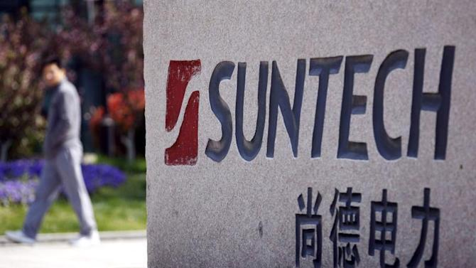 File photo of a man walking past Suntech Power Holdings' headquarters in Wuxi