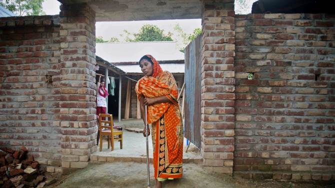 """In this photo taken Monday, May 21, 2013, Hawa Begum walks with a crutch outside the family home in Tekani village in far northwestern Bangladesh. Hawa was severely injured when she jumped out of a fifth-floor window to escape the flames that consumed the Tazreen garment factory last November. Her 18-year-old daughter Moushimi was one of the 112 workers who did not survive the fire. """"I tried to go to my daughter, but there was no way,"""" Hawa recalled. """"The gates on each floor were locked. There was smoke everywhere."""" (AP Photo/Ismail Ferdous)"""