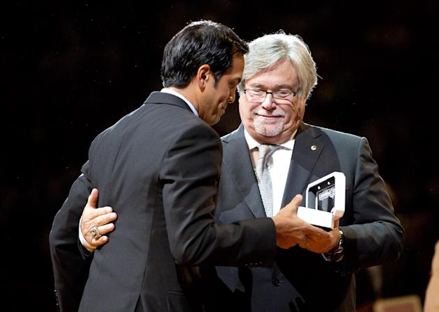 Miami Heat coach Erik Spoelstra, left, gets his championship ring from team owner Micky Arison, right, during a ceremony before their season-opening NBA basketball game against the Chicago Bulls, Tues