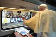 "In this picture made available by the Vatican newspaper Osservatore Romano, Pope Benedict XVI salutes from the train's window as he arrives for a peace meeting in Assisi, central Italy, Thursday, Oct. 27, 2011. The pontiff has invited Jews, Hindus, Sikhs and Muslims to a pilgrimmage to the Umbrian hilltop town of Assisi where 25 years ago Pope John Paul II, the Dalai Lama and others spent the day praying for peace amid the Cold War. The banner in background reads ""Peace"". (AP Photo/Osservatore Romano) EDITORIAL USE ONLY"