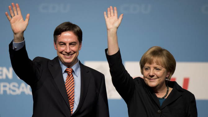 FILE - In this Jan 14, 2013 file photo, German Chancellor Angela Merkel and David McAllister, governor of the German state of Lower Saxony, wave during an election campaign rally in Stadthagen, northern Germany. Merkel is riding high in polls as she seeks a third term at the head of Europe's biggest economy. But a major state election this weekend may lift her center-left rivals' hopes of defying the odds and ousting her as Germany's leader. The Sunday balloting is one of only two significant electoral tests before national parliamentary elections. Recent polls in Lower Saxony show the Social Democrats and Greens neck-and-neck with Merkel's party and the Free Democrats. (AP Photo/dapd, Nigel Treblin, File)