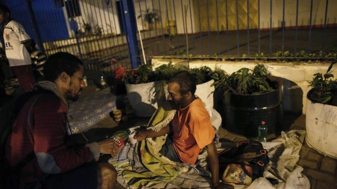 Homeless man receives food by a member of Sao Miguel Arcanjo church on a street during a free Christmas dinner in Sao Paulo