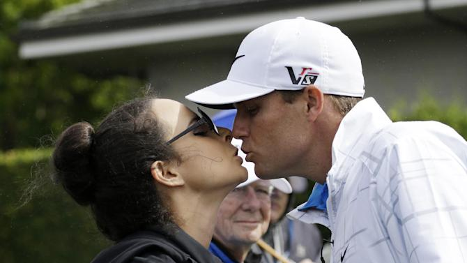 Amber Watney, left, kisses her husband, Nick Watney, after she handed him a sandwich while he was waiting to tee off in the first round at the Tournament of Champions golf tournament Friday, Jan. 4, 2013, in Kapalua, Hawaii. (AP Photo/Elaine Thompson)